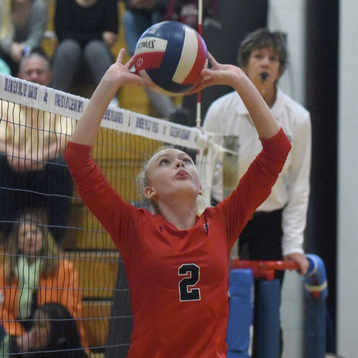 New Canaan's Elle Sneddon sets the ball during the Rams' volleyball match against Darien at Darien High School on Thursday, Oct. 17, 2019.