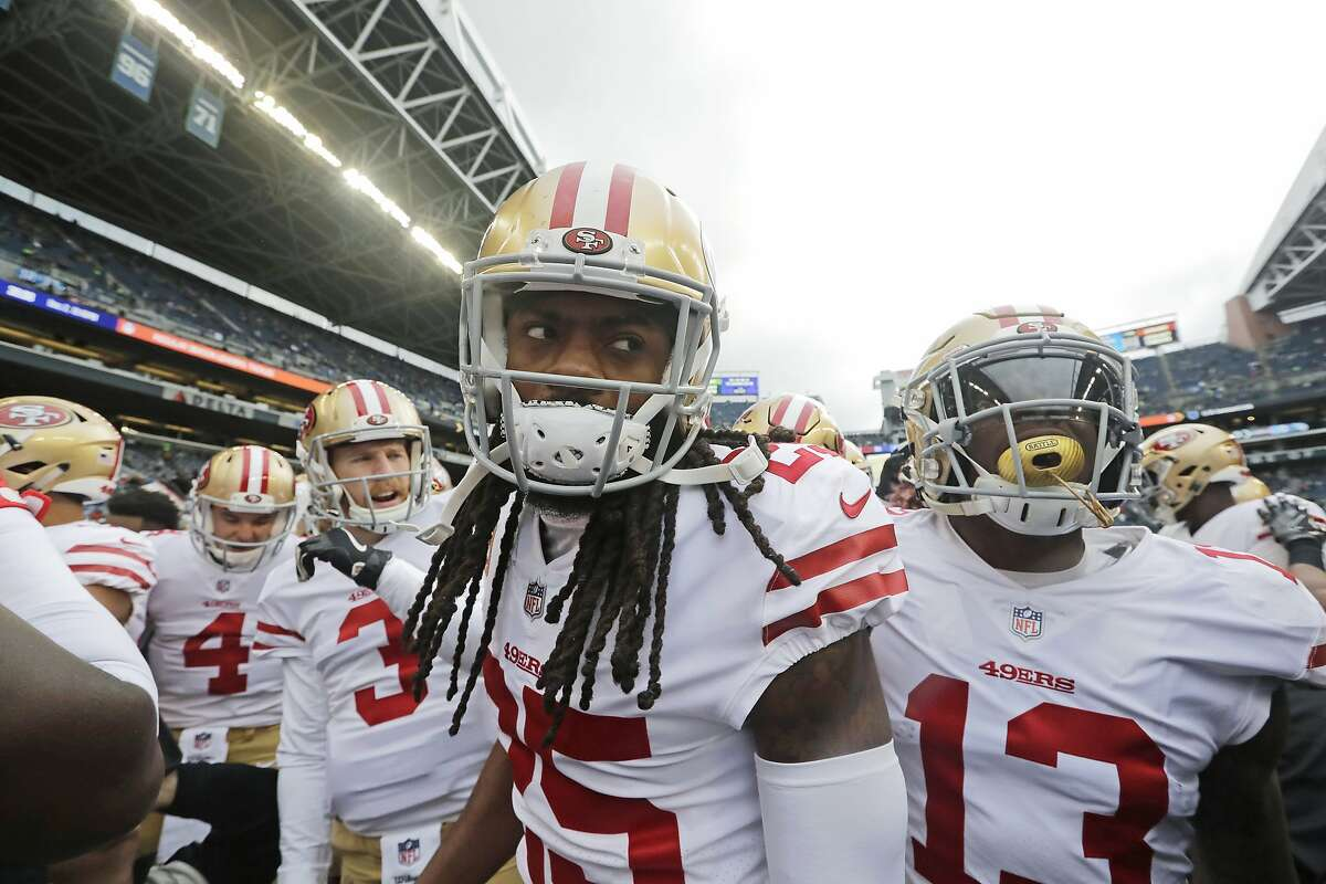 San Francisco 49ers cornerback Richard Sherman, center, huddles with teammates before an NFL football game against the Seattle Seahawks, Sunday, Dec. 2, 2018, in Seattle. (AP Photo/Elaine Thompson)