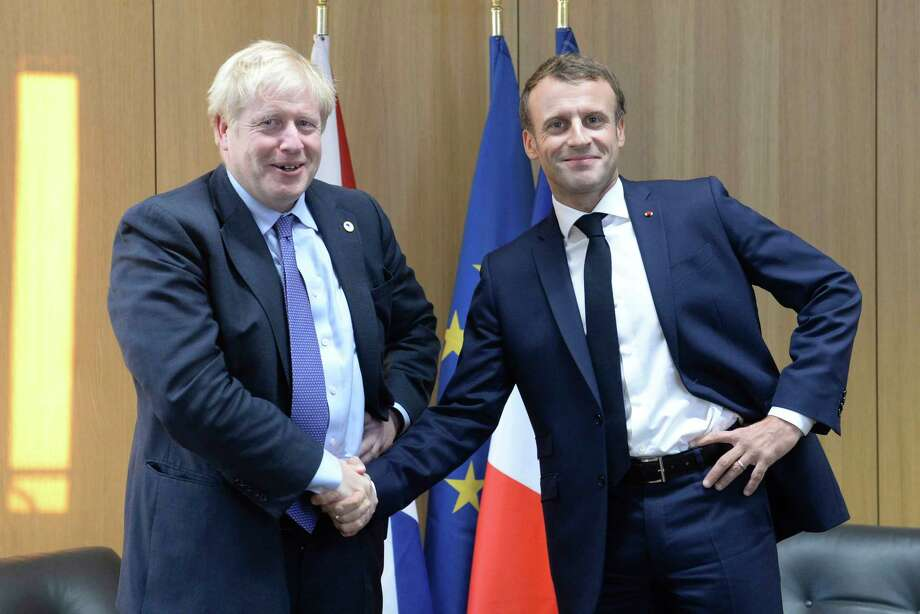 Britain's Prime Minister Boris Johnson poses as he shakes the hand of French President Emmanuel Macron, right, during a European Union leaders summit in Brussels, Belgium, Thursday Oct. 17, 2019.  Britain and the European Union reached a new tentative Brexit deal on Thursday, hoping to finally escape the acrimony, divisions and frustration of their three-year negotiation. (Johanna Geron/Pool via AP) Photo: Johanna Geron / AP