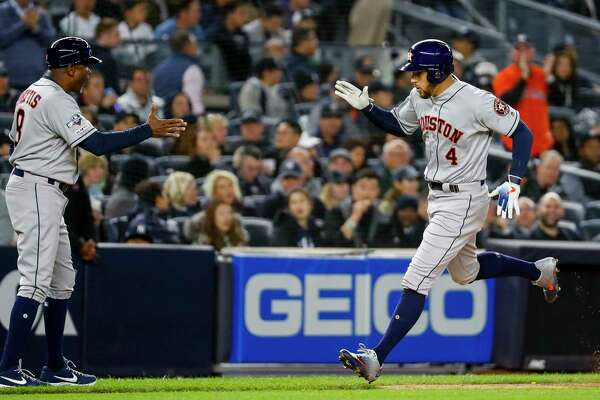 Houston Astros center fielder George Springer (4) celebrates with third base coach Gary Pettis (8) after hitting a three-run home run against New York Yankees starting pitcher Masahiro Tanaka during the third inning of Game 4 of the American League Championship Series at Yankee Stadium on Thursday, Oct. 17, 2019, in New York.