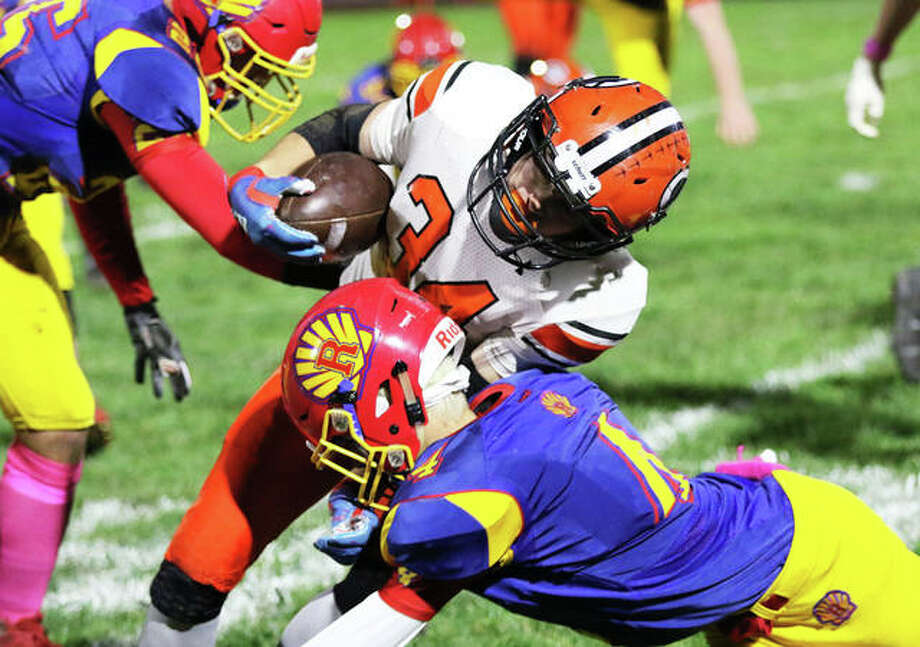 Gillespie running back John Berry is tackled by Roxana's Jacob Sido (right) in a SCC football game Friday night at Raich Field in Roxana. Photo: Greg Shashack / The Telegraph