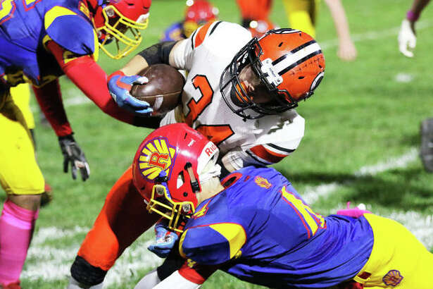 Gillespie running back John Berry is tackled by Roxana's Jacob Sido (right) in a SCC football game Friday night at Raich Field in Roxana.