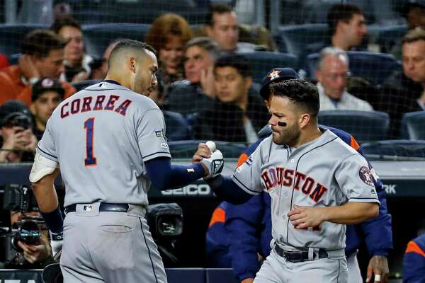 Houston Astros shortstop Carlos Correa (1) celebrates with Houston Astros second baseman Jose Altuve (27) after hitting a three-run home run against New York Yankees relief pitcher Chad Green during the sixth inning of Game 4 of the American League Championship Series at Yankee Stadium on Thursday, Oct. 17, 2019, in New York.