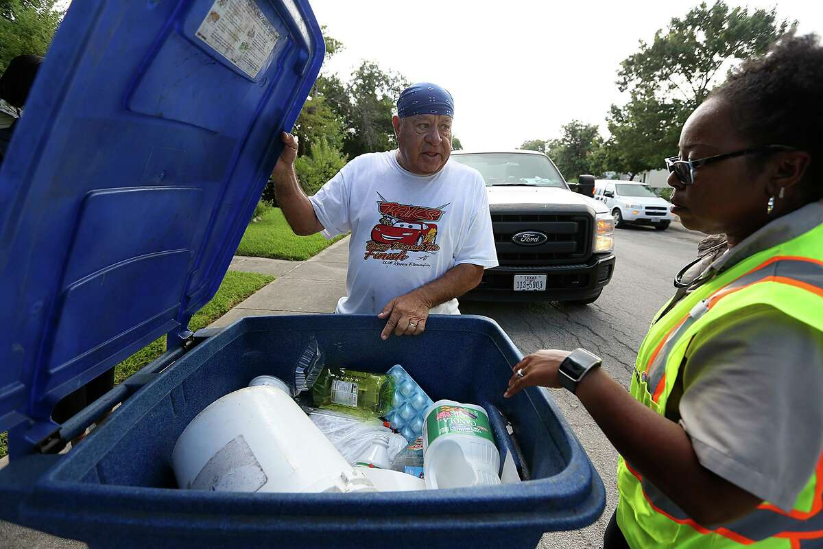 """San Antonio Solid Waste Department route inspector Asia Jones-Carr talks with homeowner Richard Gonzales in this 2015 photo. Until recycling processors change their engineering methods for efficiently separating materials, """"less is (probably) more"""" when it comes to what we put in the recycling bin."""