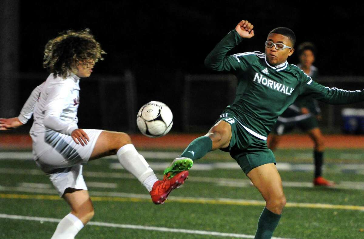 Brien McMahon's Christopher Ocampo (11), left, and Norwalk's Kevin Carabali (8) converge on the ball during boys soccer action in Norwalk, Conn., on Thursday Oct. 17, 2019.