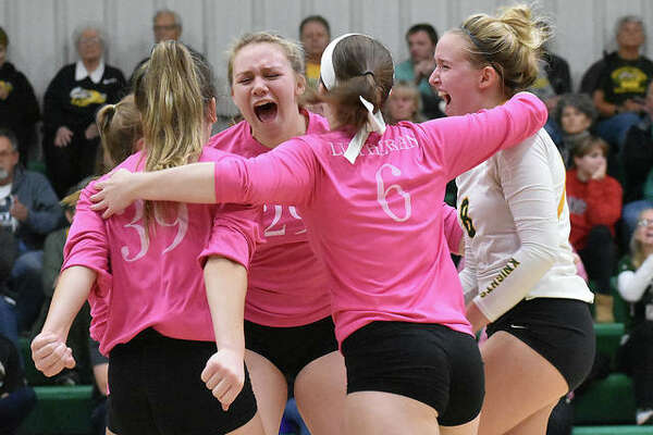 Metro-East Lutheran celebrates after claiming the final point of a three-game win over Father McGivney.