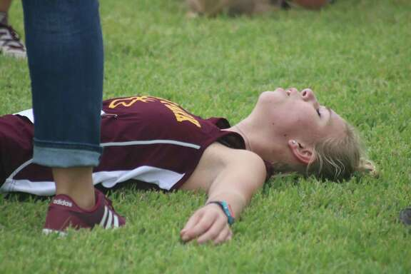 An exhausted Katie Burke lies on the ground, just past the finish line, following the 5K girls race. Burke finished with a 23:01, good for Deer Park's fifth and final scoring runner Thursday morning.