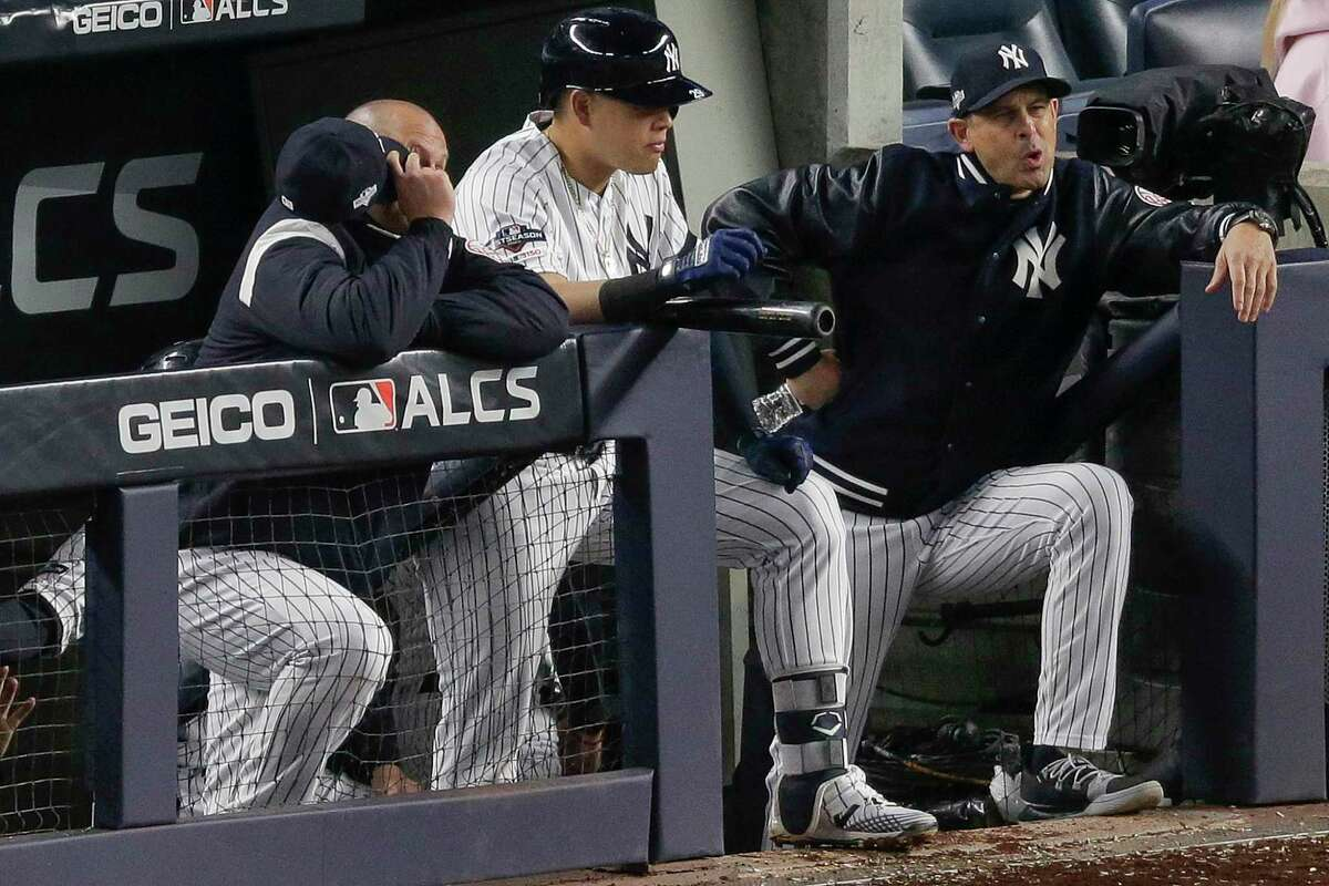 New York Yankees manager Aaron Boone, right, reacts during the eighth inning of Game 4 of baseball's American League Championship Series against the Houston Astros, Thursday, Oct. 17, 2019, in New York.