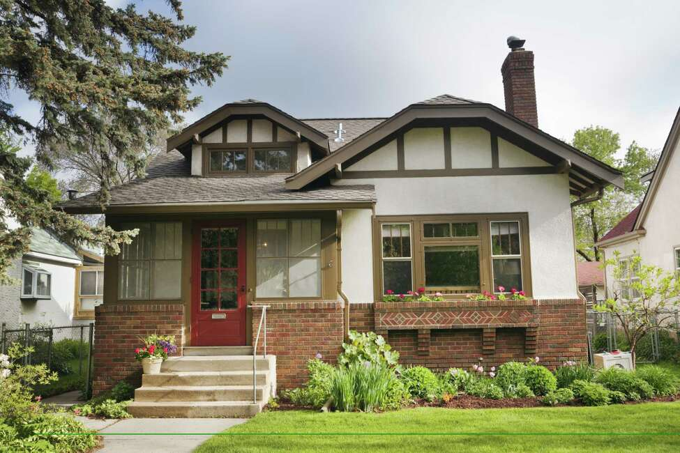 Full exterior front facade of 1920s era Arts and Crafts bungalow house. An example of Midwest, USA residential building style, the old, quaint architecture features stucco and brick walls, red front door, and picture window looking out to the lawn. A springtime flower garden grows outdoors. Horizontal, straight-on front view.