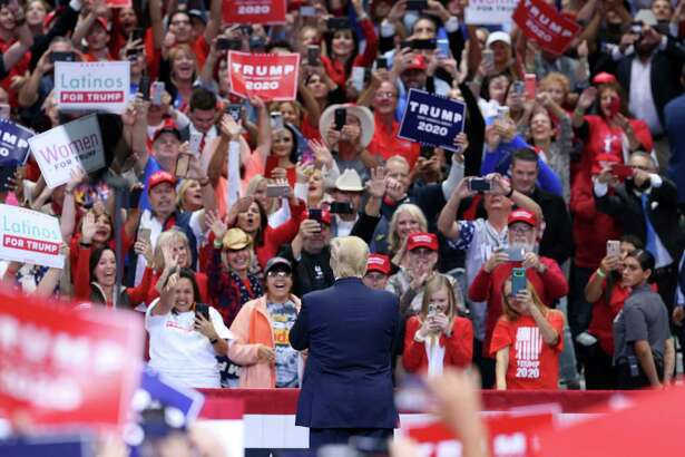 Supporters cheer and hold up placards as U.S. President Donald Trump, front, arrives on stage during a rally in Dallas, Texas, U.S., on Thursday, Oct. 17, 2019. Trump's Doral golf resort in Miami will be the site of next year's Group of Seven summit, a decision that reignited claims he's violating a constitutional prohibition against profiting from the presidency. Photographer: Dylan Hollingsworth/Bloomberg