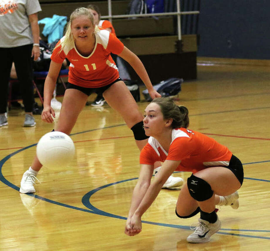 Greenfield's Jessa Vetter (right) goes low to receive a serve while teammates Kersty Gibbs watches the play during an Oct. 5 match at Carlinville. The Tigers earned their season's 20th victory Thursday against North Greene. Photo: Greg Shashack / The Telegraph