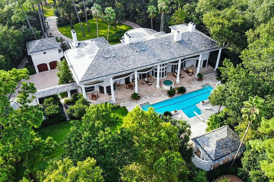 This secluded $13.7 million Memorial mansion is perfect for entertaining. At more than 15,000 square feet, the palatial home offers five bedrooms, eight full and three half bathrooms and a backyard getaway featuring a 75-foot pool with race lanes, three water falls and a spa, open-air cabana with a bathroom and shower and full summer outdoor kitchen. Photo: TK Images/Tad Krampitz