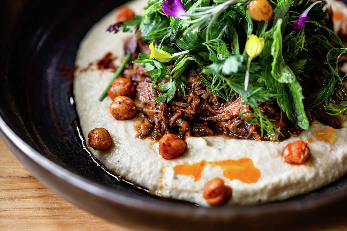 Braised lamb shank on garlic hummus with crispy chickpeas, herb salad and grilled flatbread at Traveler's Table.