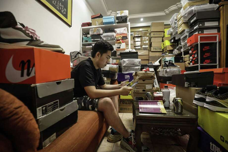 Tian Hao, a sneaker collector and trader, browse through one of the trading apps while sitting among boxes of shoes crammed into the living room of his apartment in Beijing on Sept. 25, 2019. Photo: Bloomberg Photo By Qilai Shen. / The Washington Post