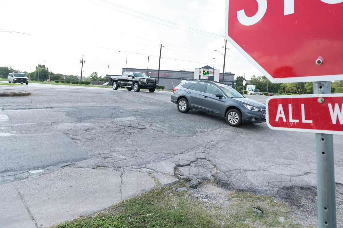 Vehicles drive though the West 20th Street and T C Jester intersection over a portion of deteriorating roadway on Oct 7, 2019, in Houston.