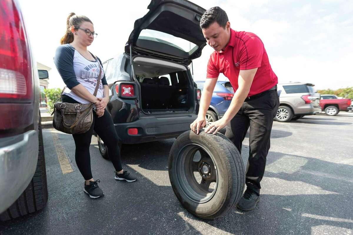 Discount Tire employee Chris Guerra shows Jordan Hamil a sidewall bubble in her tire at the T C Jester store on Oct 7, 2019, in Houston.