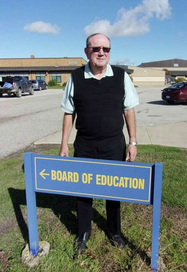 Kinde native John Moore stands next to the North Huron Schools Board of Education sign. Moore has a long history at North Huron, from being a student to serving as the superintendent for 20 years. (Rich Harp/For the Tribune)