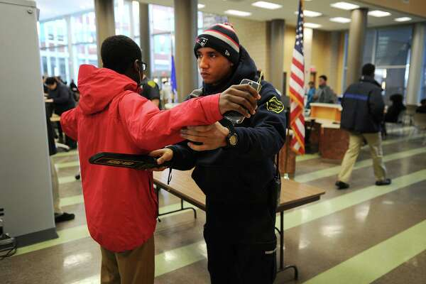 A school security officer wands a student at the start of the school day in Connecticut in 2015. A reader says it's time for Texas schools to install metal detectors.