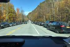 Cars line the shoulder along Route 73 in the Adirondacks High Peaks region.