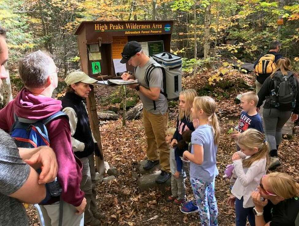 Volunteer trailhead stewards with the Adirondack 46er group advise a family on what likes ahead along the Cascade Mountain trail.