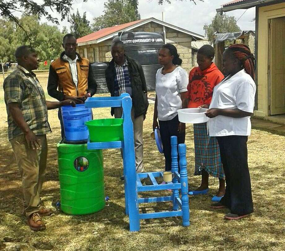 Kenyan villagers receive instructions on how to care for their new water filter. Photo: Contributed / Connecticut Post