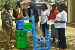 Kenyan villagers receive instructions on how to care for their new water filter.