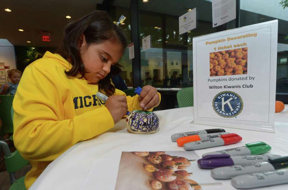Wilton resident Cristine Perez, 8, decorates a pumpkin at the Kiwanis table during The Wilton Library's annual Innovation Day last year. Innovation Day this year is Saturday, Oct. 19. Photo: Erik Trautmann / Hearst Connecticut Media / Norwalk Hour