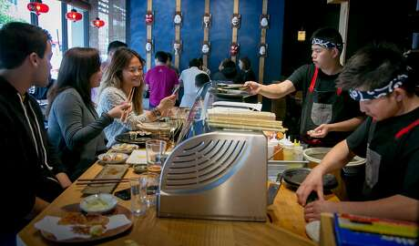 People have lunch sitting at the Sushi bar at Okane in San Francisco, Calif., on May 6th, 2016.