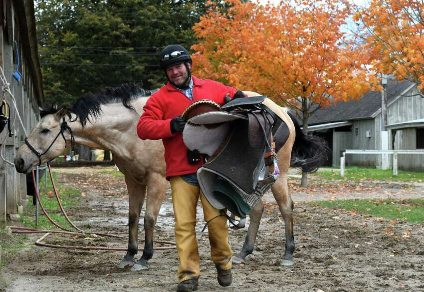 Bronc Vogele takes his saddle back to the barn following morning workouts at the Oklahoma Training Track on Friday, Oct. 18, 2019, in Saratoga Springs, N.Y. (Will Waldron/Times Union)