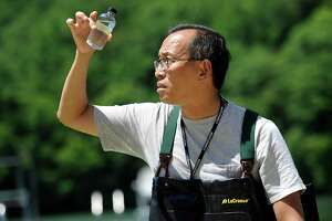 Edwin Wong, a biology professor at Western Connecticut State University, takes a sample of water from the beach at Lynn Demning Park in New Milford, Thursday, July 21, 2016. That sample will be tested for toxins.