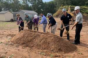 Town officials, led by Mayor Enzo Faienza, center in blue dress shirt, break ground for the new Public Works/WPCA facility. The officials include at left Alice Kelly, chairwoman of the WPCA, and Public Works Director Louis J. Spina and Town Engineer Jon Harriman in dark blue polo shirts to Faienza's immediate left.