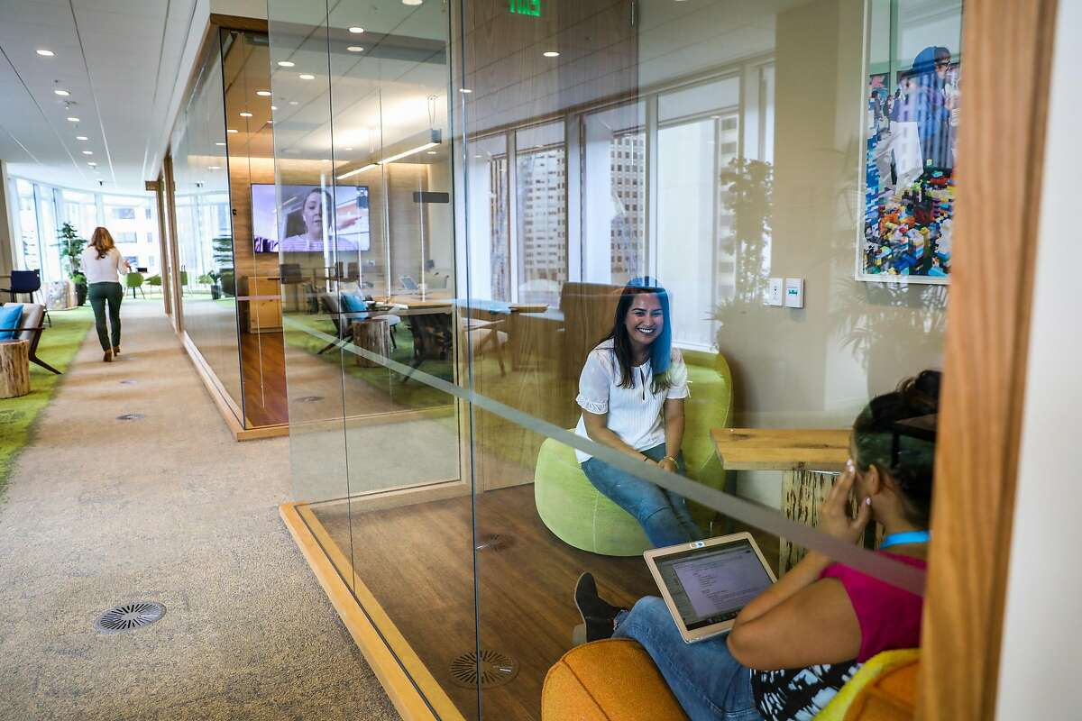 Salesforce employees Shantel Villarroel (right) and Pooja Deopura (center) work on the 8th floor of the Salesforce tower in San Francisco, California, on Wednesday, Sept. 12, 2018.