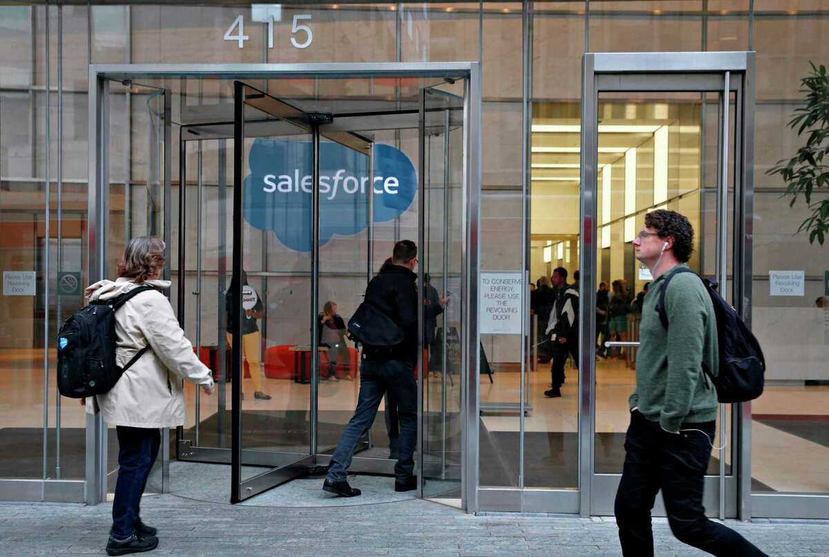 Office workers walk to their jobs in front of Salesforce Tower at Fremont and Mission streets in San Francisco in 2019. Salesforce said its workforce will go remote permanently beyond the coronavirus pandemic, with most employees only coming into the office a couple times a week.