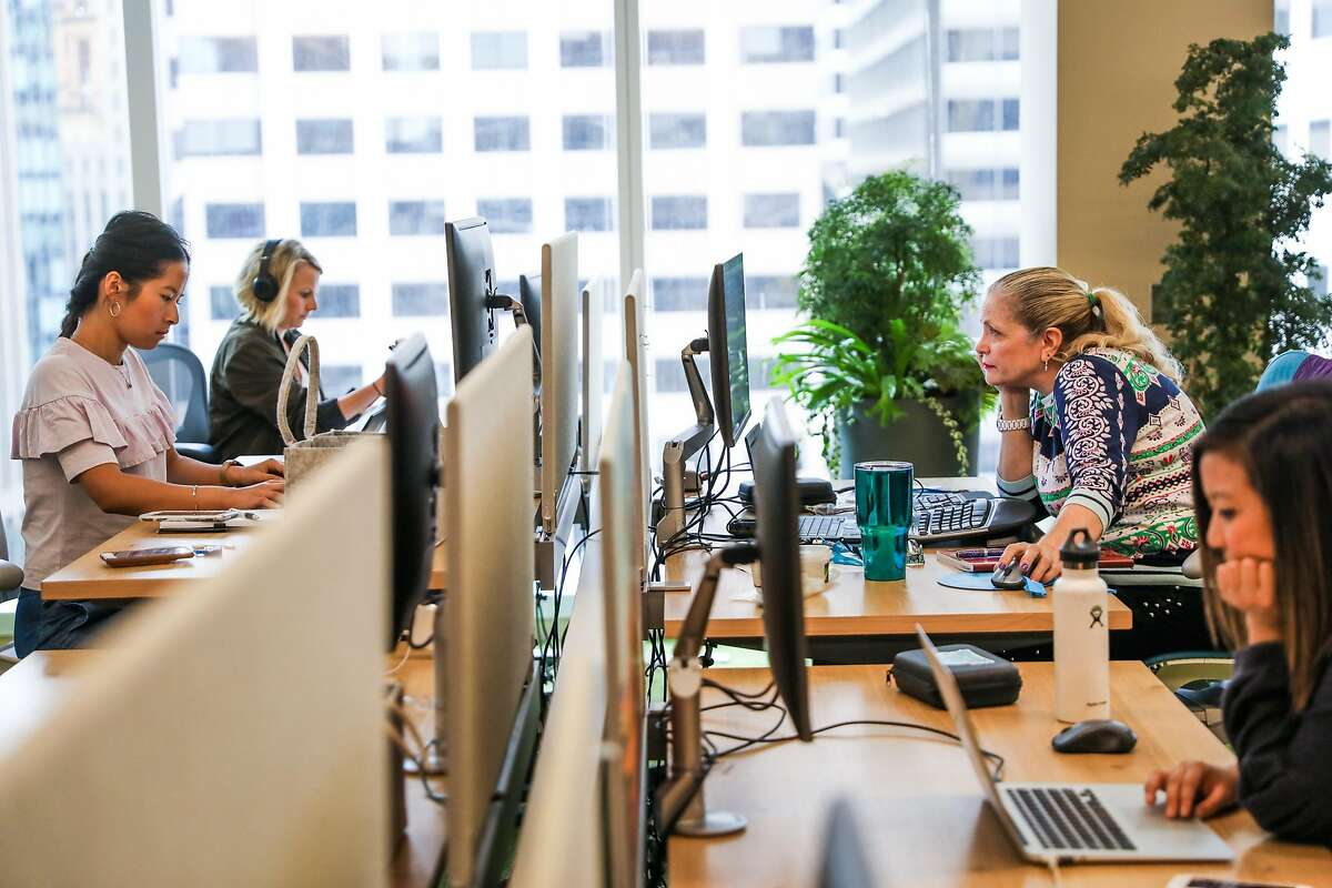Salesforce employee Branwyn Fearn (second from right) works with colleagues at a desk on the 8th floor of the Salesforce Tower in San Francisco, California, on Wednesday, Sept. 12, 2018.