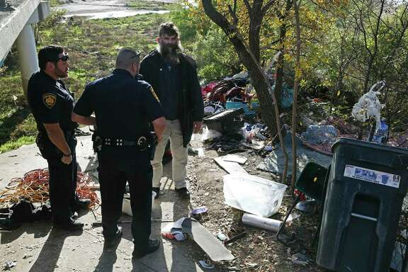 Leland Ray Wood, 51, formerly of Lancaster, California, talks with San Antonio Fear Free Environment Officers Johnny Perez, left, and Elliott Valdez, at an encampment by a bridge on Culebra Road, Dec. 4, 2018. The city is receiving help from California to address homelessness. A reader finds it ironic.