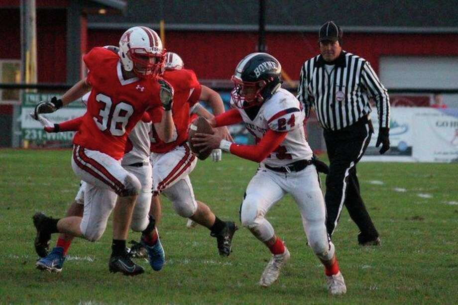 Henry Koehne (38) brings pressure up the middle to send the Boyne City quarterback running for his life. (Photo/Robert Myers)