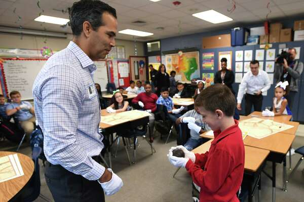 Texas Land Commissioner George Bush hands a historic cannonball to Christian Jenkins at Dishman Elementary on Friday. Bush attended the school to give a Texas history lesson. The cannonball was fired at the Alamo by the Mexican Army. Photo taken Friday, 10/18/19