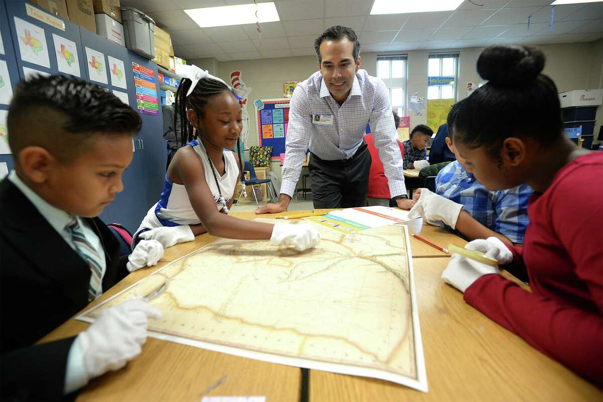 Texas Land Commissioner George Bush shows a historical Texas map to fourth grade students at Dishman Elementary on Friday. Photo taken Friday, 10/18/19