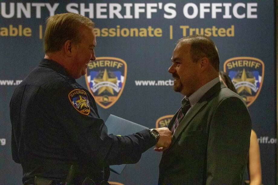 Sheriff Rand Henderson straightens maintenance supervisor Mathew Veith's tie before they turn for a photo during the Montgoemry County Sheriff's Office promotion and awards ceremony Thursday, October 17, 2019 at the Lone Star Convention Center in Conroe. Photo: Cody Bahn, Houston Chronicle / Staff Photographer / © 2019 Houston Chronicle