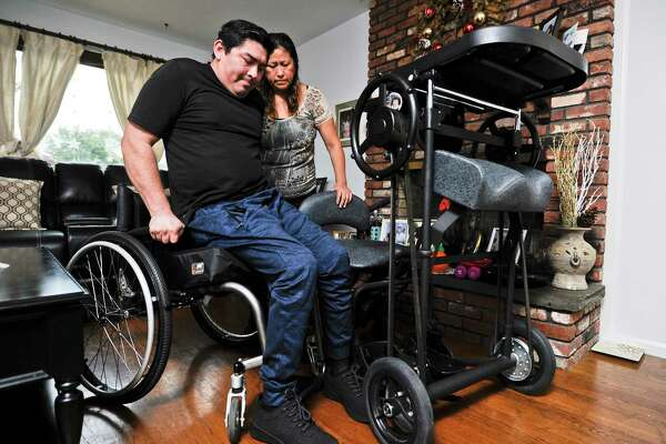 Gladys Rivera helps her husband Amando Uribe from his wheelchair into an Easystand 5000 mobility device on Oct. 16, 2019 at their home in Stamford Connecticut. Uribe, a Stamford resident and food truck owner who was in an accident earlier this year took to GoFundMe to raise money for his medical costs, raising almost $10,000. Some of the proceeds were used to purchase the Easystand 5000, which costs over $5000, but he was able to find a used system for just under a thousand dollars.