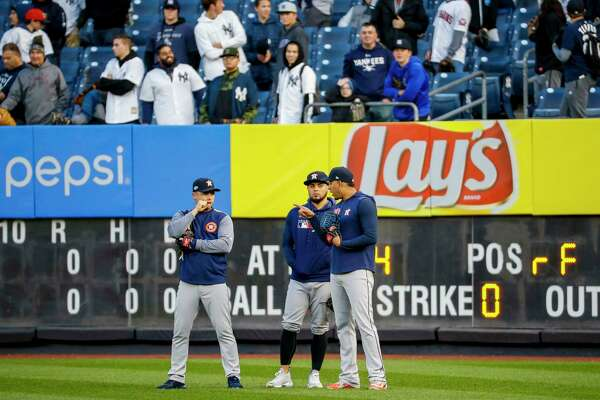 Houston Astros second baseman Aledmys Diaz, left to right, relief pitcher Roberto Osuna, and left fielder Michael Brantley talk on the outfield during batting practice before Game 5 of the American League Championship Series at Yankee Stadium on Friday, Oct. 18, 2019, in New York.