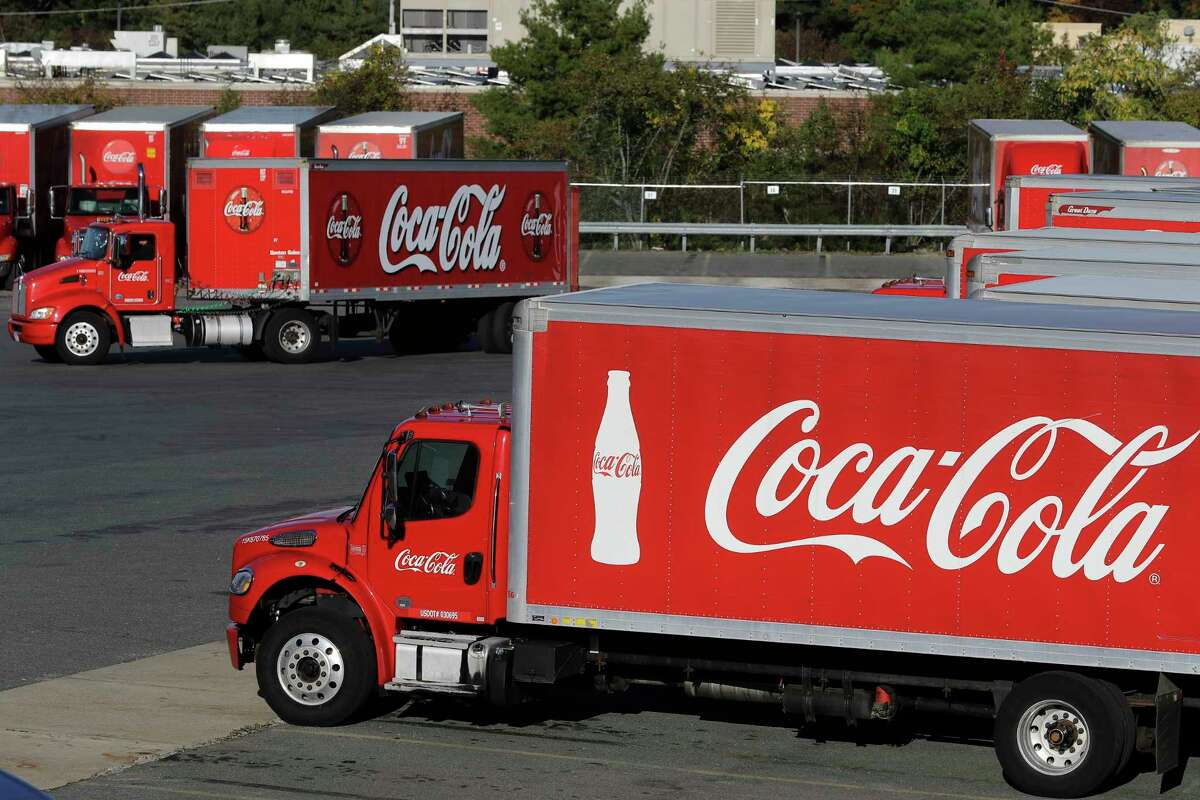 In this Monday, Oct. 14, 2019 photo a truck with the Coca-Cola logo, behind left, maneuvers in a parking lot at a bottling plant in Needham, Mass. The Coca-Cola Co. reports financial results Friday, Oct. 18. (AP Photo/Steven Senne)