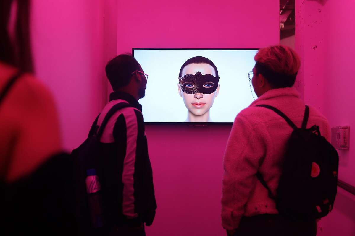 Visiting students from English Language Institue SF watch an Ashley Madison Angels at Work in San Francisco exhibition in a secret room of �The Glass Room�, a new pop-up exhibition which just opened on Wednesday, Oct. 16, 2019, in San Francisco, Calif.