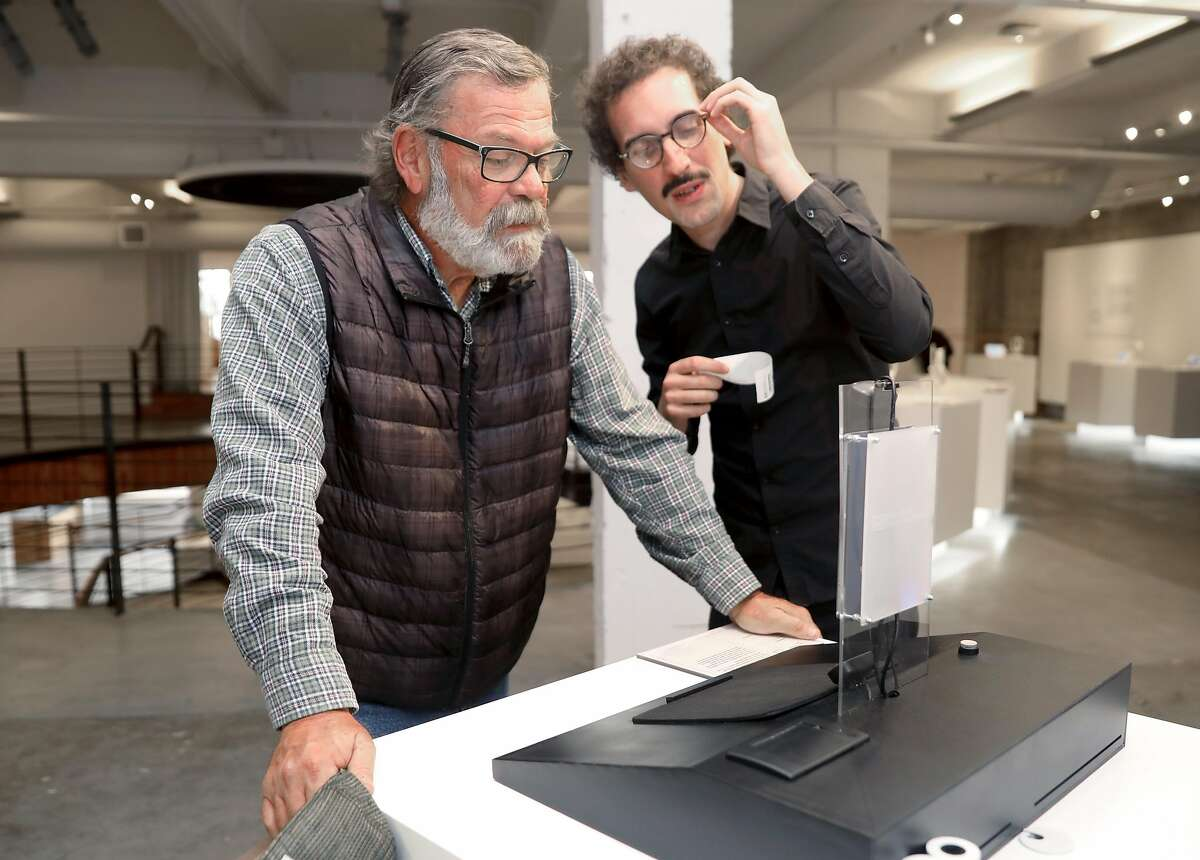 Artist Manual Beltran (right) shows Michael King (left) from Hayward visiting �The Glass Room�, a new pop-up exhibition, and shows how to use his exhibition which explores the production of data comparatives as a form of labor seen on Wednesday, Oct. 16, 2019, in San Francisco, Calif.