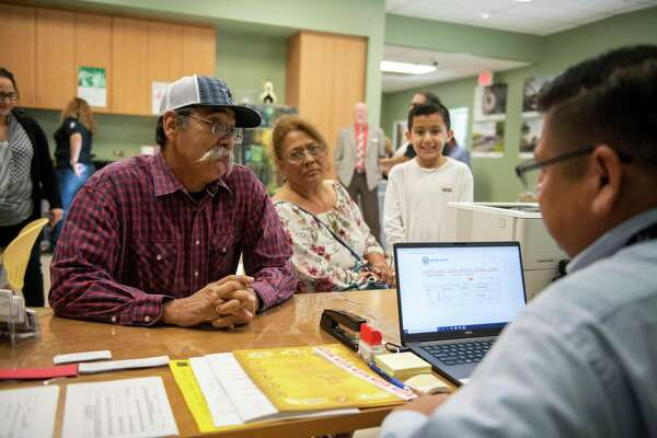 Manual Garcia, left, speaks with staff member Rafael Are, as his wife Gloria Garcia and grandson Bently Serna, 8, look on during a Bexar County during a mobile unit launch, allowing residents to buy marriage licenses, record real property records or military discharge papers, register an assumed business name or cattle brand and more away from the courthouse.