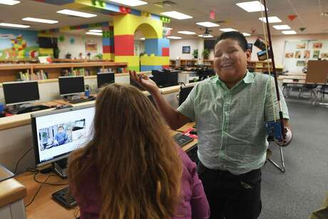 Kevin Vazquez, 11, born with one hand, smiles as librarian Sandra Welzenbach shows him pictures from the internet of children with only one hand who are able to play music with the help of special devices. On Friday, a group of educators at Villarreal Elementary School presented him with a device they built that will allow him to play the violin. Kevin inherited a love of music from his father, who died when he was 4.