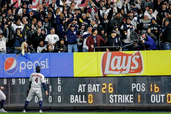 Houston Astros center fielder Jake Marisnick (6) and right fielder George Springer (4) look to the stands as fans try to catch the solo home run by New York Yankees first baseman DJ LeMahieu during the first inning of Game 5 of the American League Championship Series at Yankee Stadium on Friday, Oct. 18, 2019, in New York.