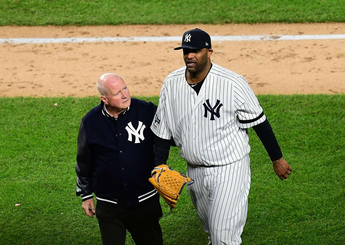 NEW YORK, NEW YORK - OCTOBER 17: Head athletic trainer Steve Donohue walks CC Sabathia #52 of the New York Yankees off the field during the eighth inning of game four of the American League Championship Series against the Houston Astros at Yankee Stadium on October 17, 2019 in the Bronx borough of New York City. (Photo by Emilee Chinn/Getty Images)