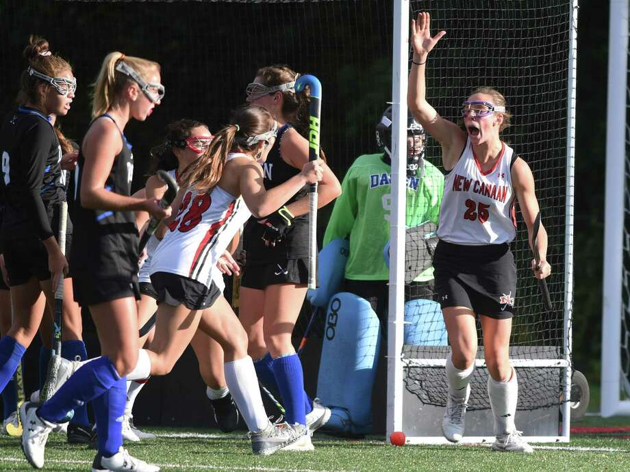 The New Canaan Rams, including Polly Parsons-Hills (25) and Marlee Smith (28) celebrate a goal in the first half during their field hockey game against Darien at Dunning Field on Friday, Oct 18, 2019. Photo: Dave Stewart / Hearst Connecticut Media / Hearst Connecticut Media