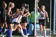 The New Canaan Rams, including Polly Parsons-Hills (25) and Marlee Smith (28) celebrate a goal in the first half during their field hockey game against Darien at Dunning Field on Friday, Oct 18, 2019.